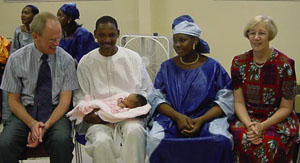 Jack and Sharon Schwille have generously supported international students in many  ways. Here they help celebrate a new baby with parents Mamadou Baldé and his wife  Aminatou, who brought the warmth and culture of Guinea to campus.