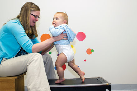 Janet Hauck holds son Charlie, 9 months, on a pediatric treadmill, which was designed to see if babies at risk for obesity that have more physical activity early in life have a changed weight trajectory as they age.
