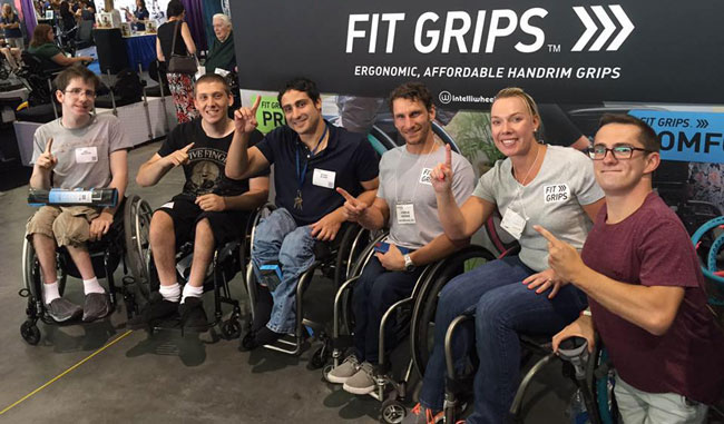 MSU Kinesiology graduate Marissa Siebel-Siero promotes her company alongside wheelchair racer Josh George (to her right) and members of a youth sled hockey team.