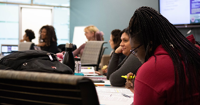 Students take notes and listen during an MSU Dialogues session.