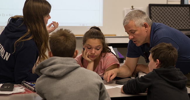 Dean Hanton works with students at their desks in the classroom.