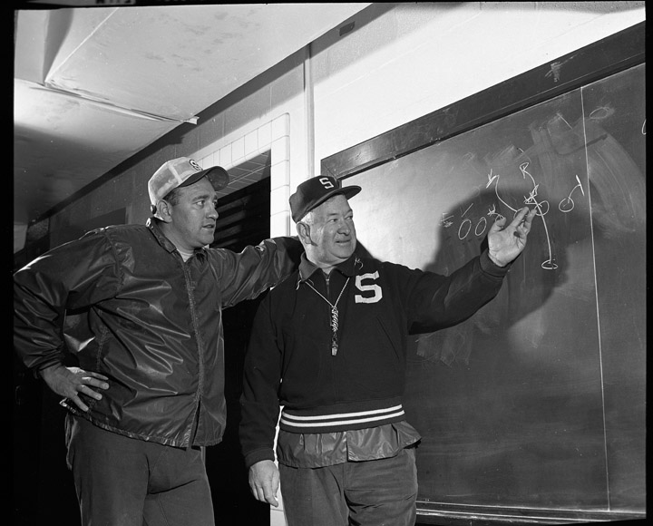 "Henry ""Hank"" Bullough (left) looks over the shoulder of MSU head football coach Duffy Dougherty in 1968. Photo courtesy of University Archives."