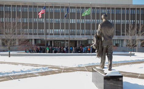 Individuals gather outside the Hannah Administration Building.