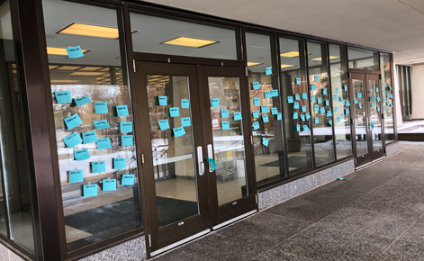 """I March for..."" cards line the windows at the Hannah Administration Building."