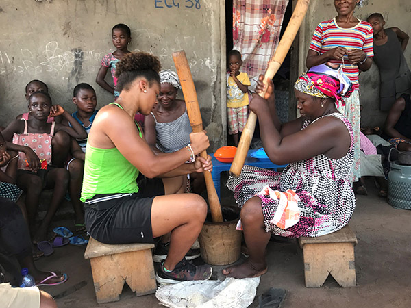 MSU student working with woman to make food.