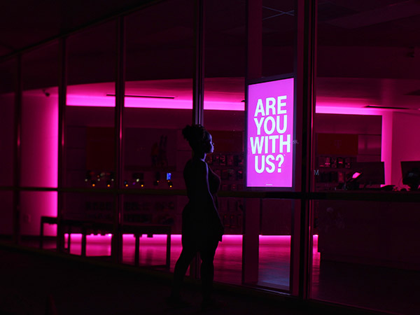 "Woman standing in front of lit sign saying ""Are you with us?"""