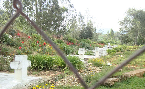 The Nyange Memorial site is outdoors. Several grave sites can be seen in the shot through a chain-link fence. Flowers and trees surround, with bricks and other building structure elements lying nearby.