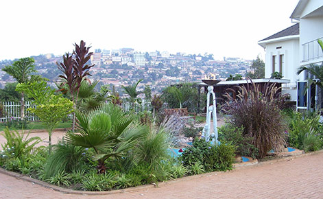 Kigali Genocide Memorial (a courtyard with plants), and Kigali, Rwanda in the background.