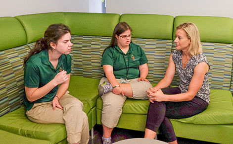Marisa Fisher (far right) speaks with two Spartan Project SEARCH interns.