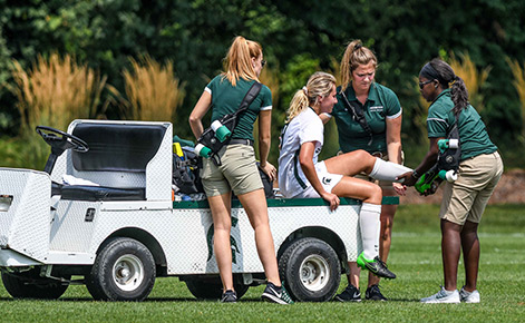 Spartan athletic trainers help an injured player on the field.