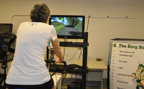 Adult on exercise bike and video game screen