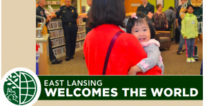 Mother holds a baby in a library setting. Underneath, the title for the event: EAST LANSING WELCOMES THE WORLD.